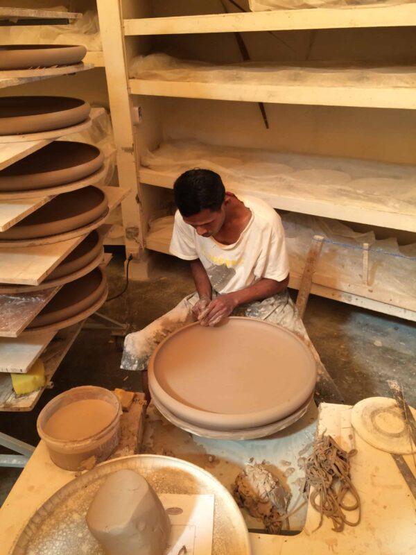 Man making ceramic bowl on pottery wheel