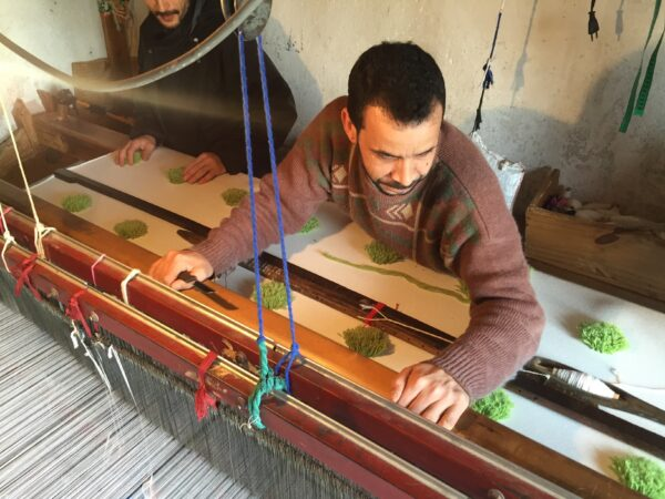 man weaving on big loom
