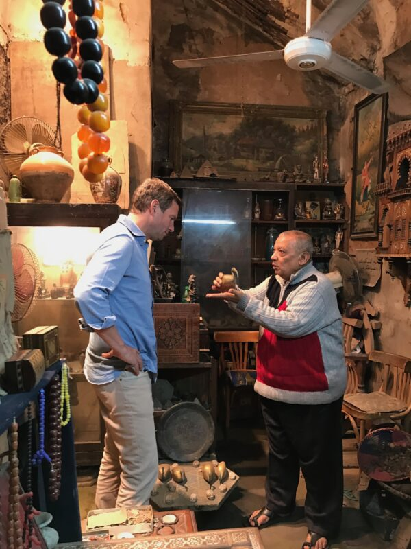 Jamie speaking to man in colorful shop lined with paintings