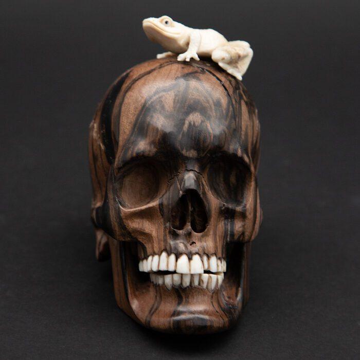 Wood skull with a carved moose antler frog