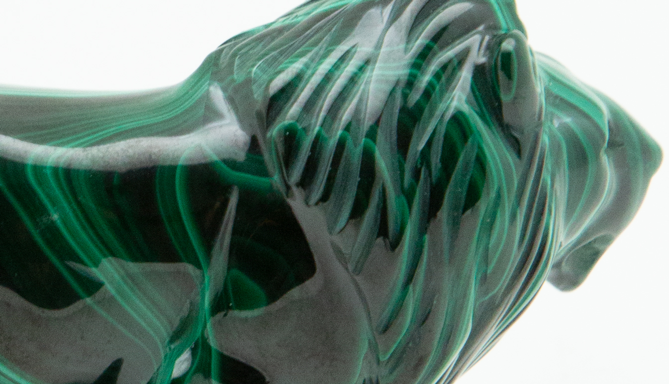 Zoom on Small malachite lion carving colored in black and green