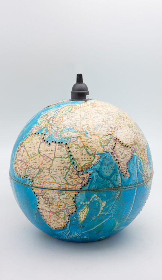 Close-up on a blue spherical globe with yellow card. Black button on the top for the cord