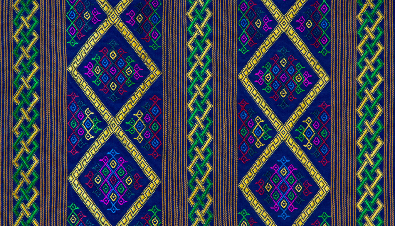 closeup of Large Rectangular Textile with Green Stripes, Yellow Diamonds, on Deep Blue Base with Red and yellow Accents