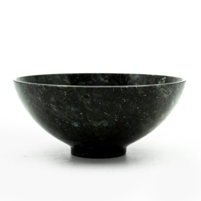 zomm on a black bowl of labradorite on a white background