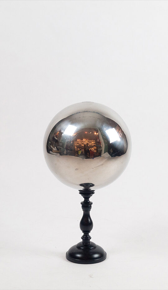 A stainless steel butler's ball mounted on a turned wooden base.