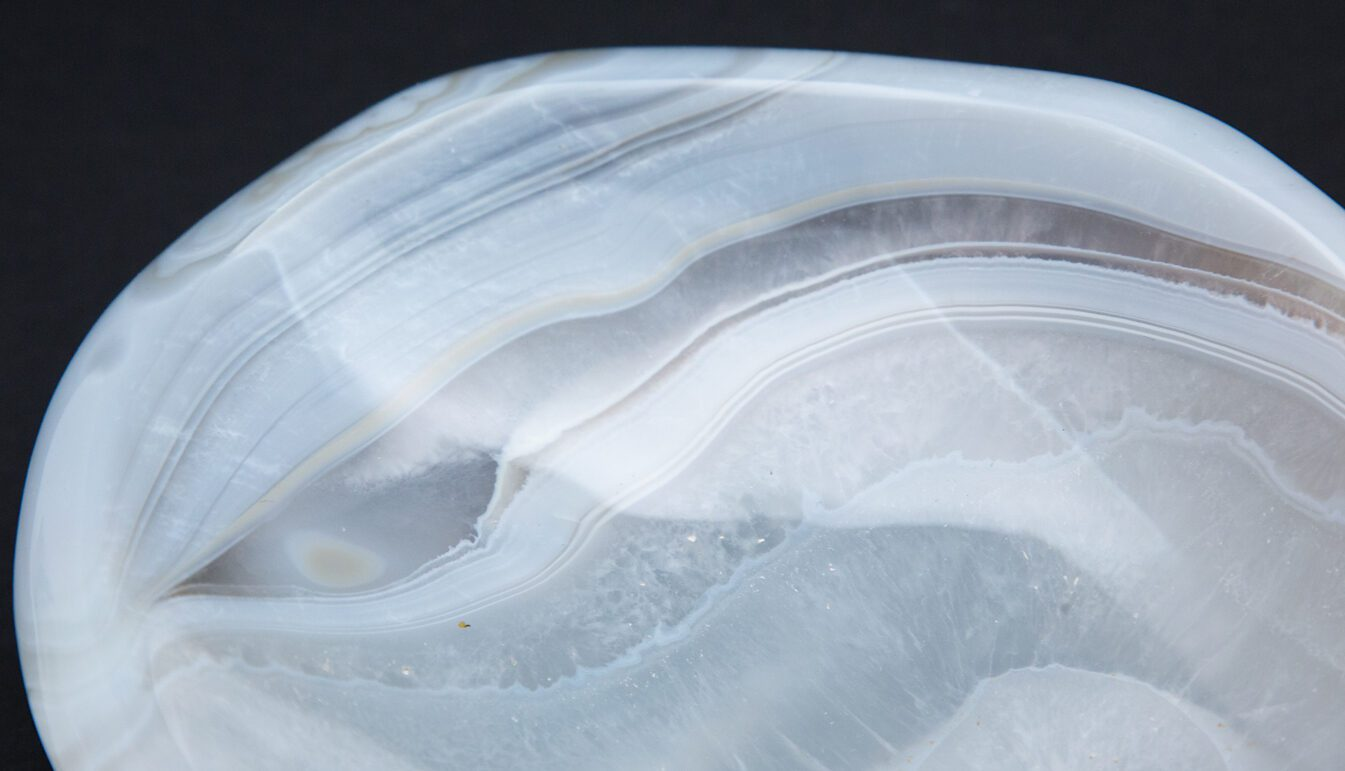 closeup of Agate vide poche with bands of light blue, white, brown, with amorphous shape. Resting on black background