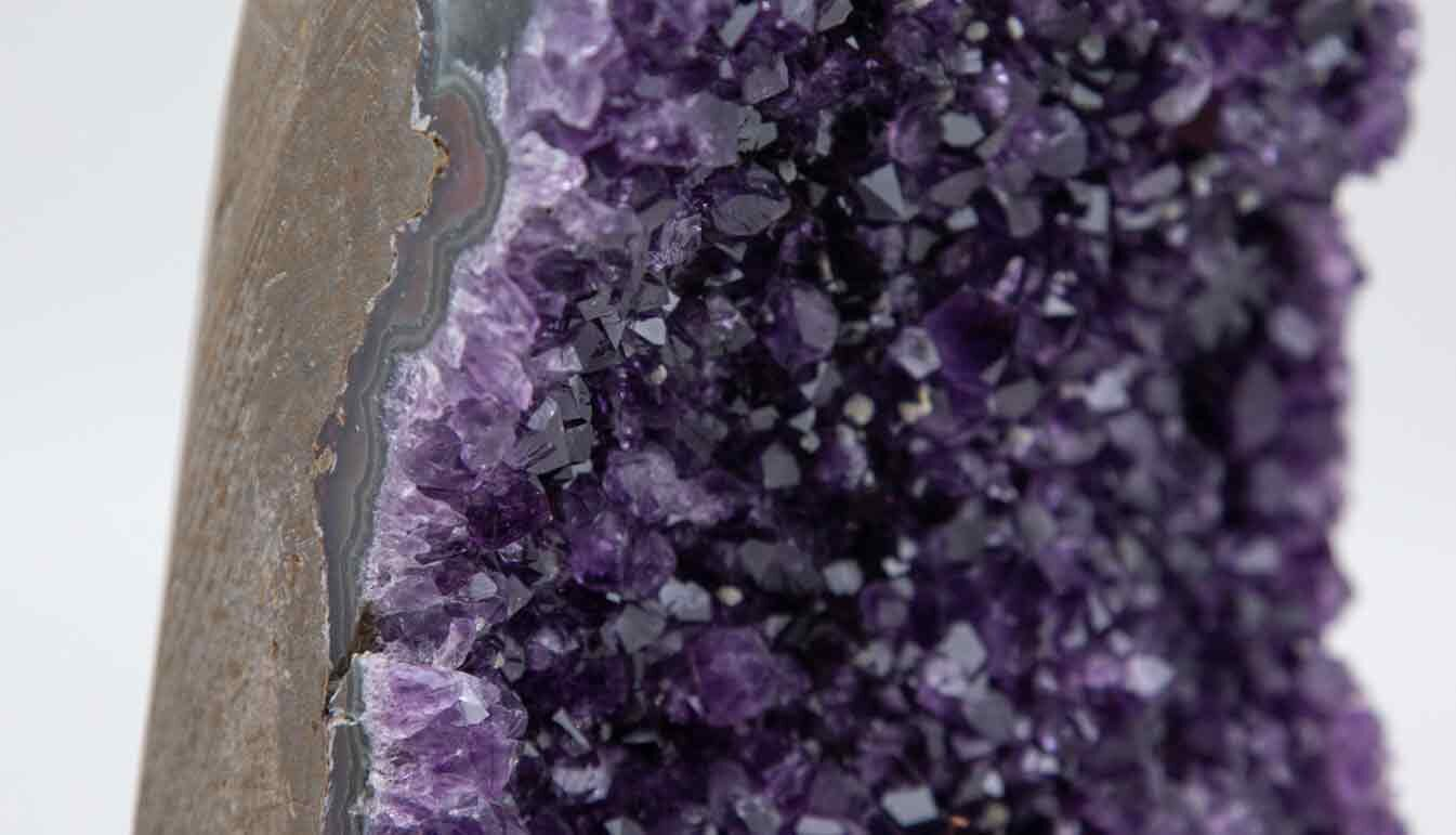 detail of large amethyst geode purple on black stand