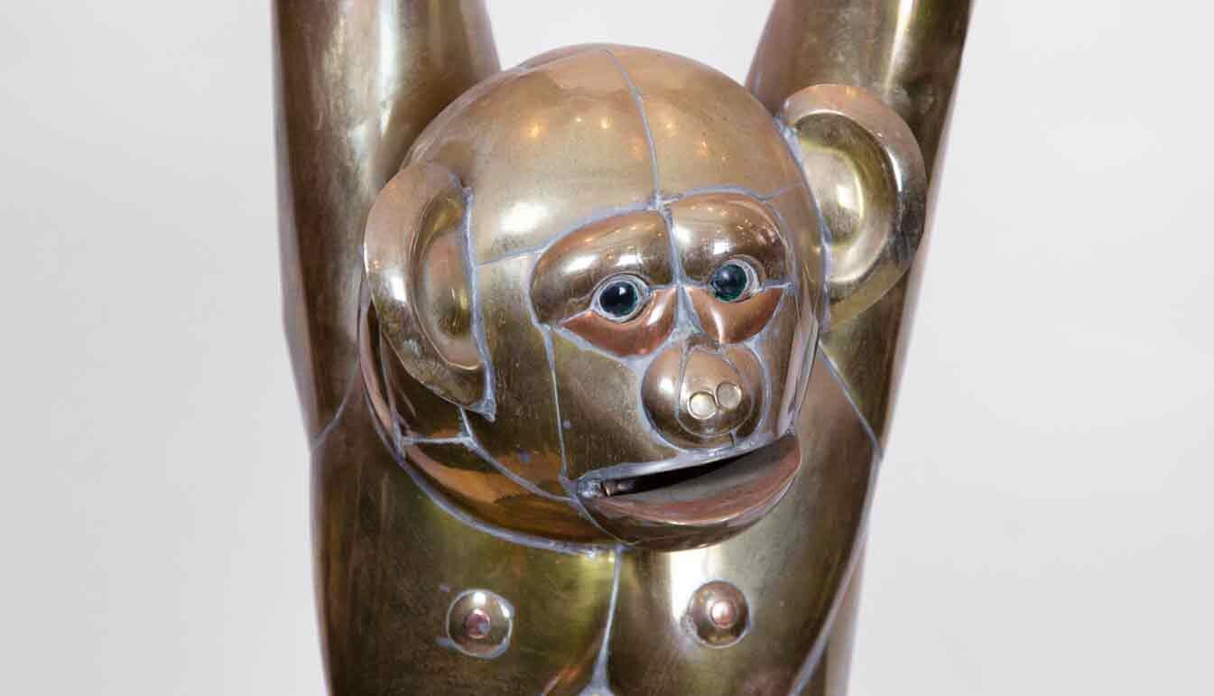 closeup of bustamente brass monkey hanging from bar